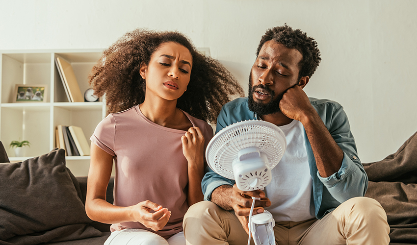 A man and woman try to cool off in front of a fan