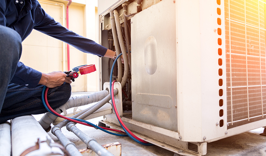 An HVAC technician diagnoses a commercial HVAC unit leak