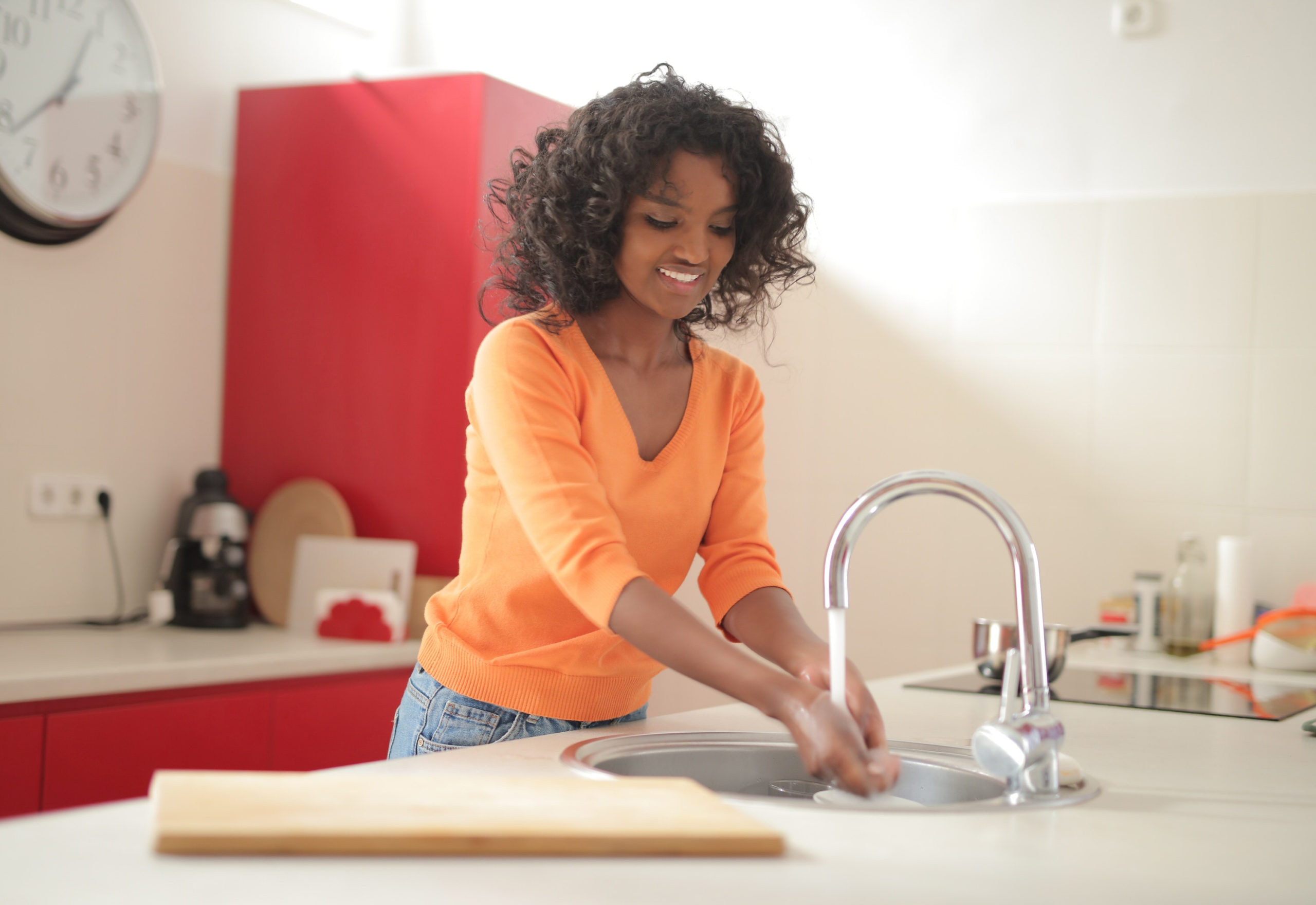 Image of young woman washing hands in sink